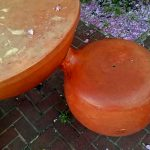 Close -up photo of bright orange bulbous table and attached seat of a Baltimore street