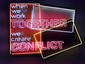 "neon sign reading ""when we work togther, we create conflict"""